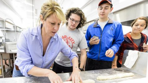 Michelle Clasen (left), of Clasen's Bakery, demonstrates how to roll bread dough to students during a Fermented Food and Beverage class taught by Nick Smith.